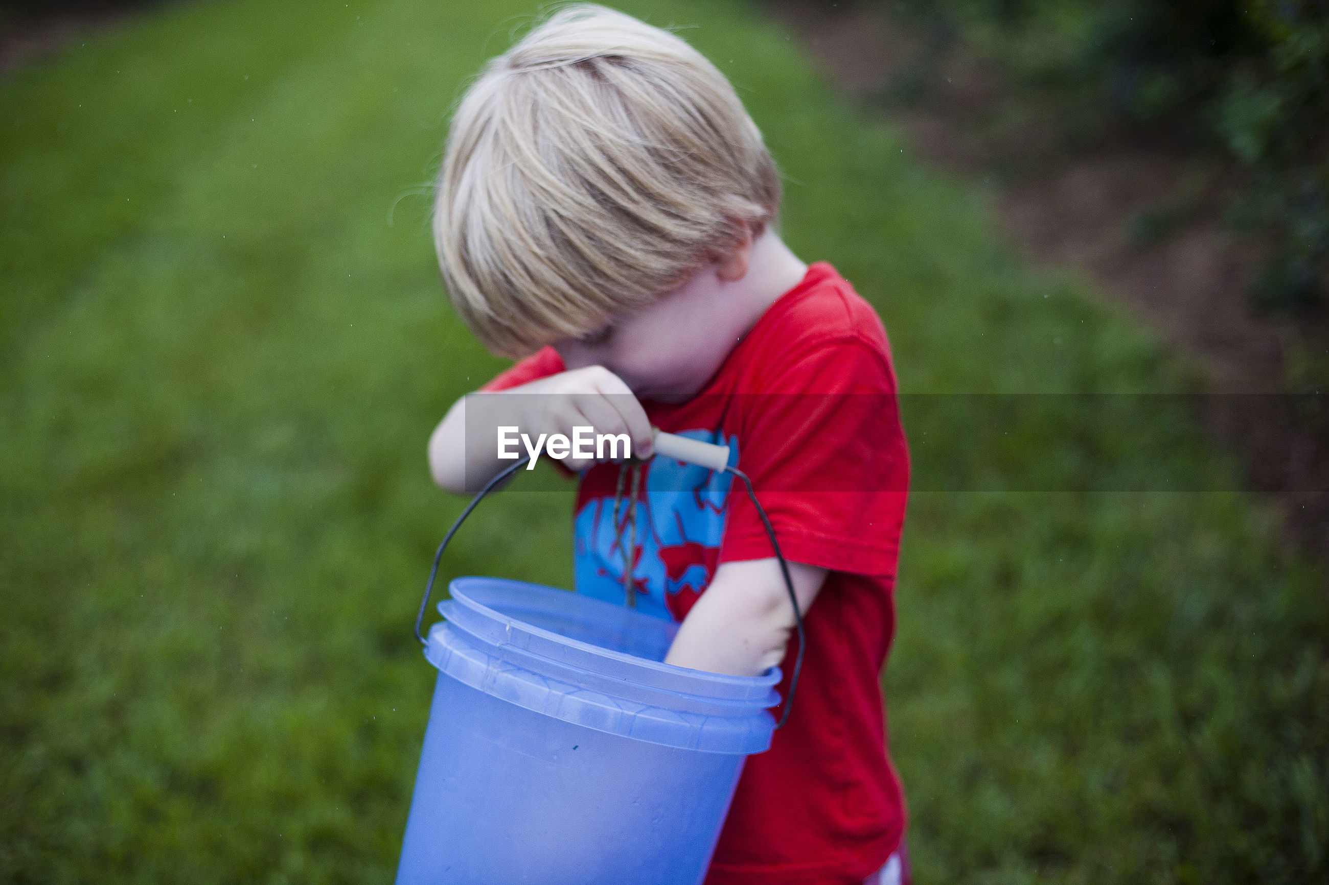 Boy holding bucket while standing on grassy field at park