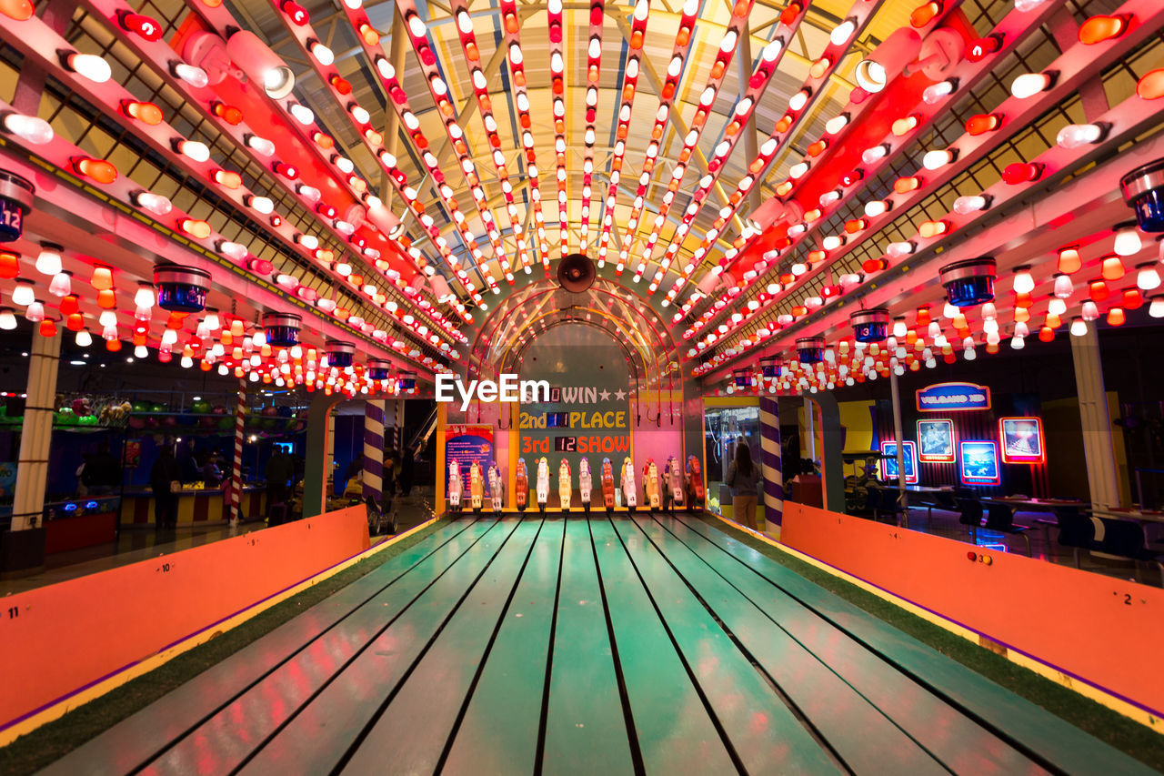 illuminated, lighting equipment, architecture, built structure, indoors, night, ceiling, incidental people, glowing, multi colored, direction, decoration, amusement park ride, the way forward, amusement park, rail transportation, transportation, arts culture and entertainment