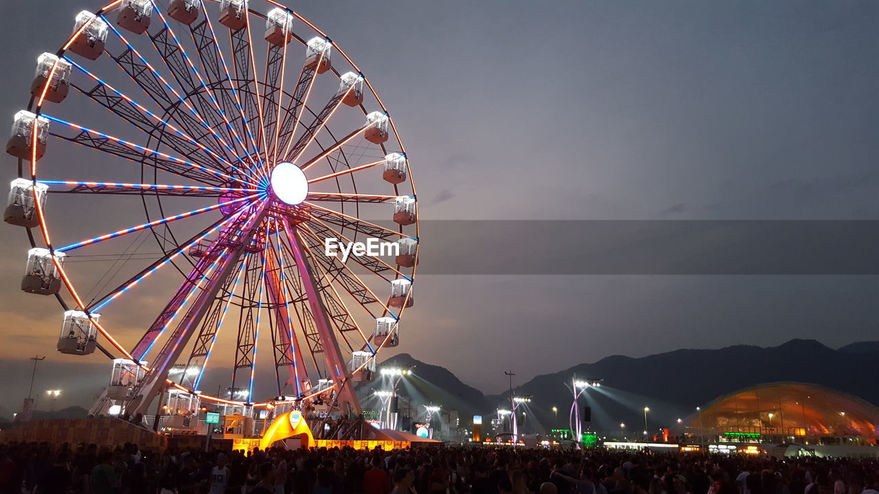 amusement park, amusement park ride, arts culture and entertainment, sky, ferris wheel, illuminated, leisure activity, nature, night, architecture, enjoyment, fairground, built structure, low angle view, outdoors, group of people, fun, crowd, spinning, nightlife