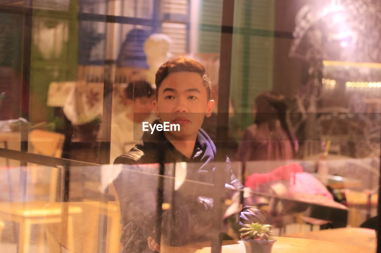Thoughtful young man seen through glass at cafe