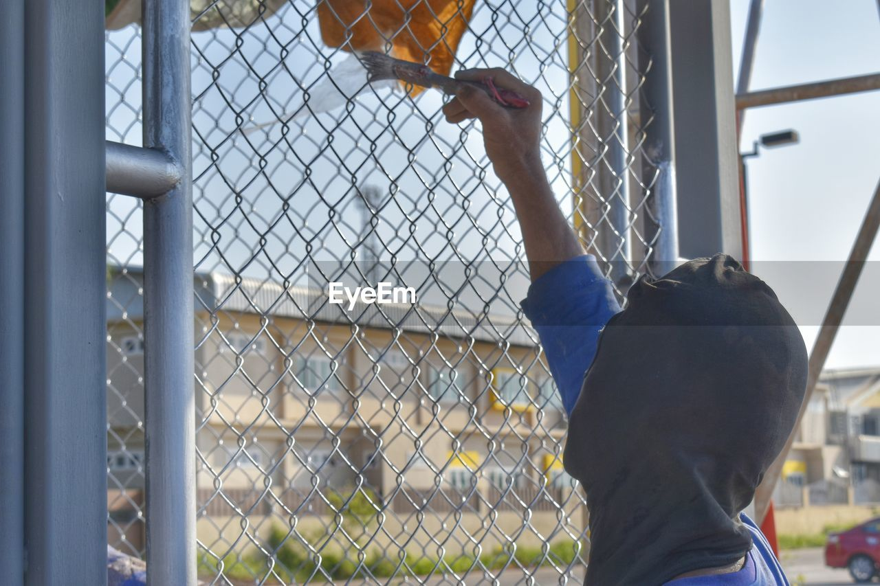fence, real people, chainlink fence, barrier, men, boundary, one person, security, safety, protection, day, metal, leisure activity, males, lifestyles, sport, boys, child, outdoors, arms raised