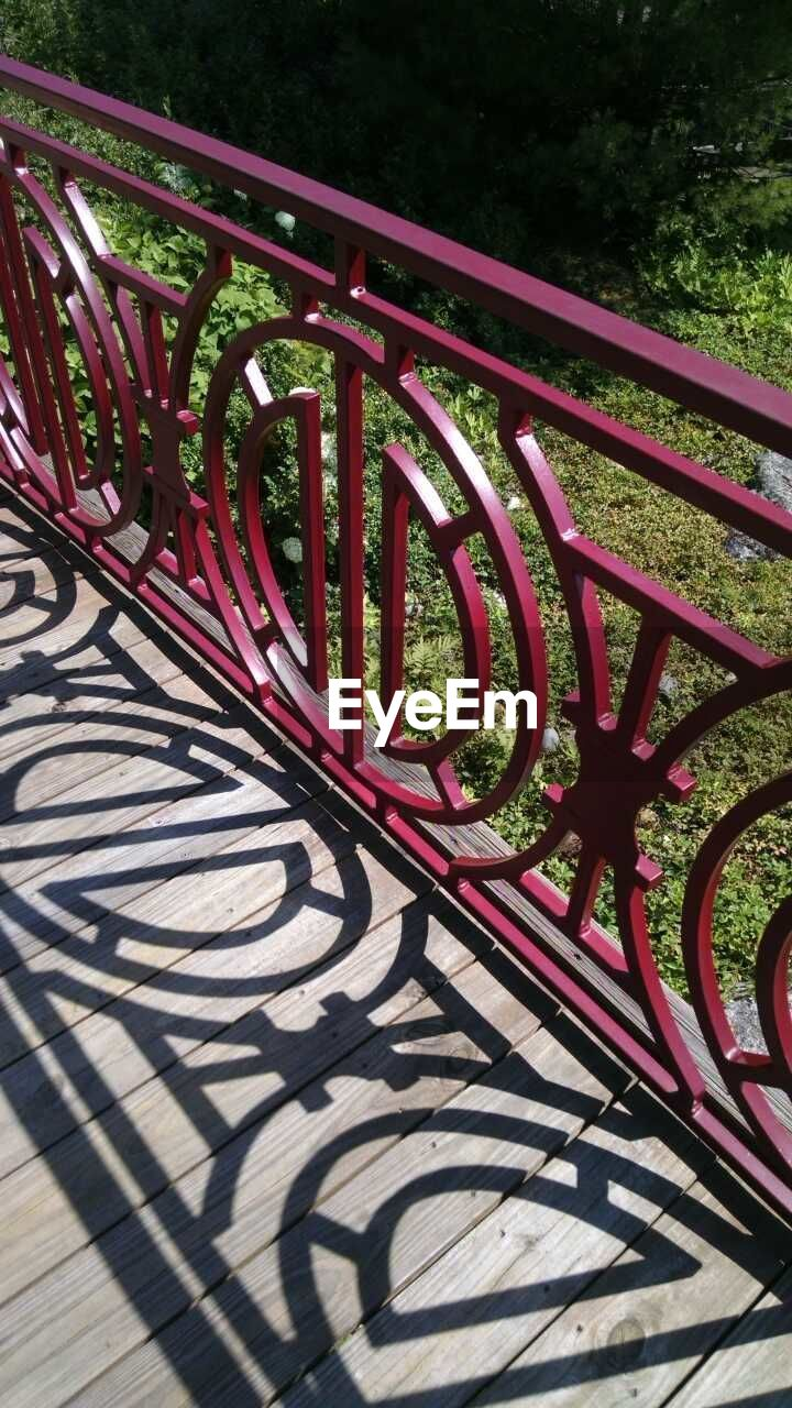 railing, high angle view, outdoors, shadow, day, no people, sunlight, bicycle rack, red, nature, close-up