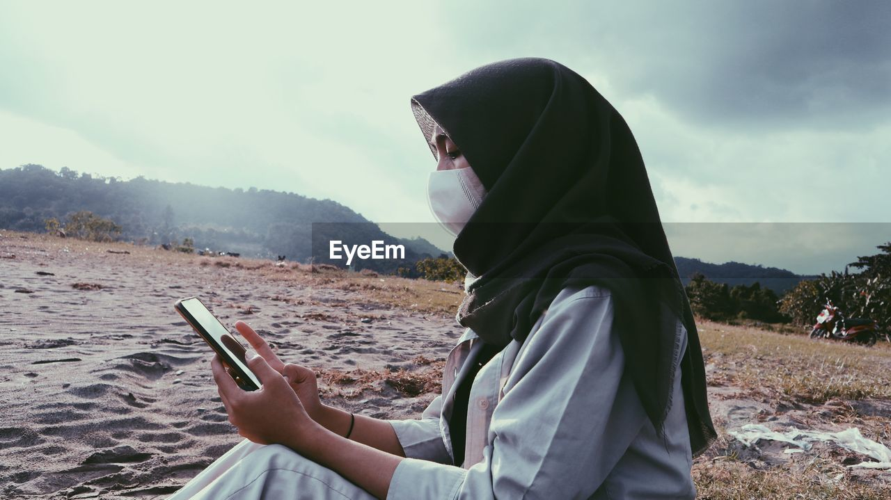Side view of young woman wearing mask using mobile phone against sky