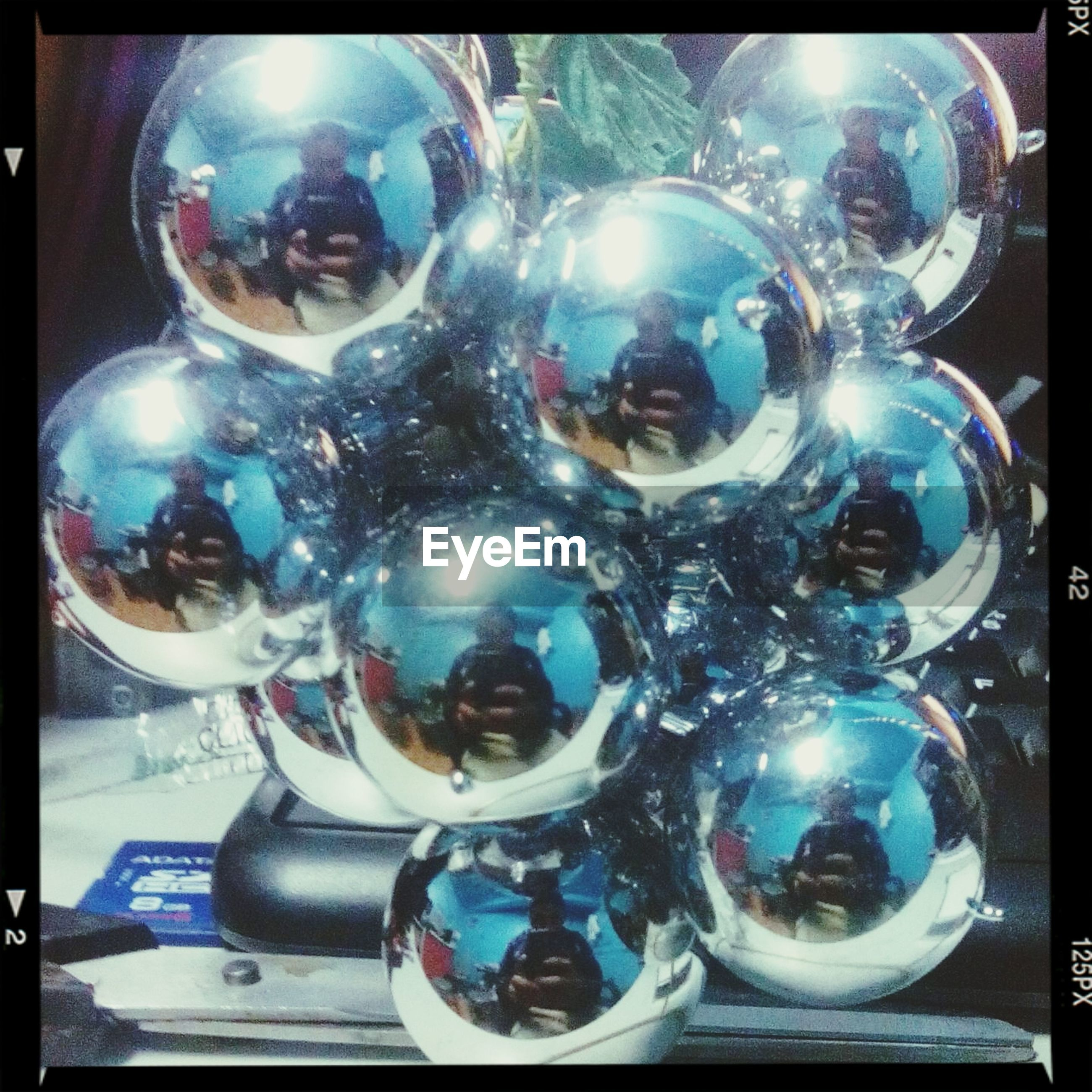 transfer print, auto post production filter, indoors, glass - material, illuminated, lighting equipment, close-up, luxury, decoration, transparent, shiny, sphere, still life, blue, no people, hanging, table, celebration, glowing, decor