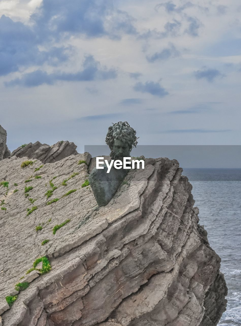sky, sea, solid, art and craft, day, nature, no people, sculpture, water, representation, rock, beauty in nature, horizon over water, cloud - sky, statue, rock formation, rock - object, horizon, land, outdoors, eroded