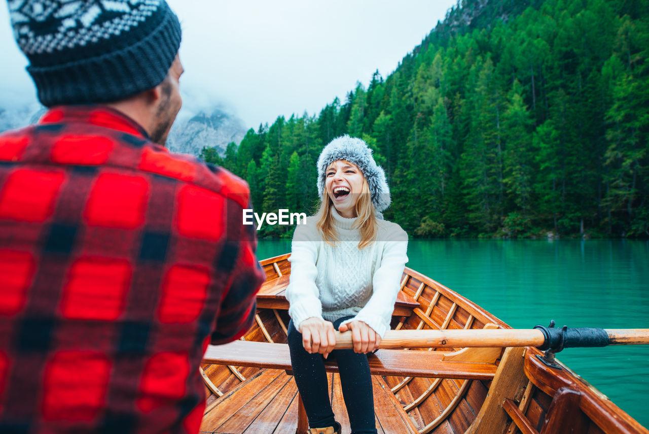 Smiling woman with man sitting in rowboat at lake