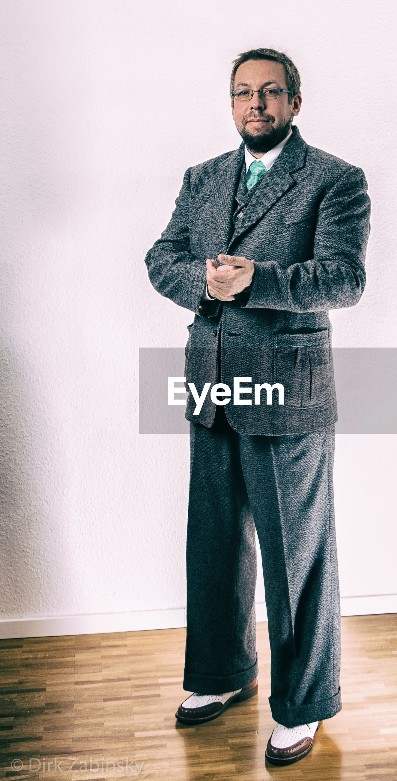 business, businessman, suit, one person, young adult, copy space, corporate business, portrait, looking at camera, full length, standing, indoors, men, occupation, real people, well-dressed, eyeglasses, one man only, day, people, adult, adults only