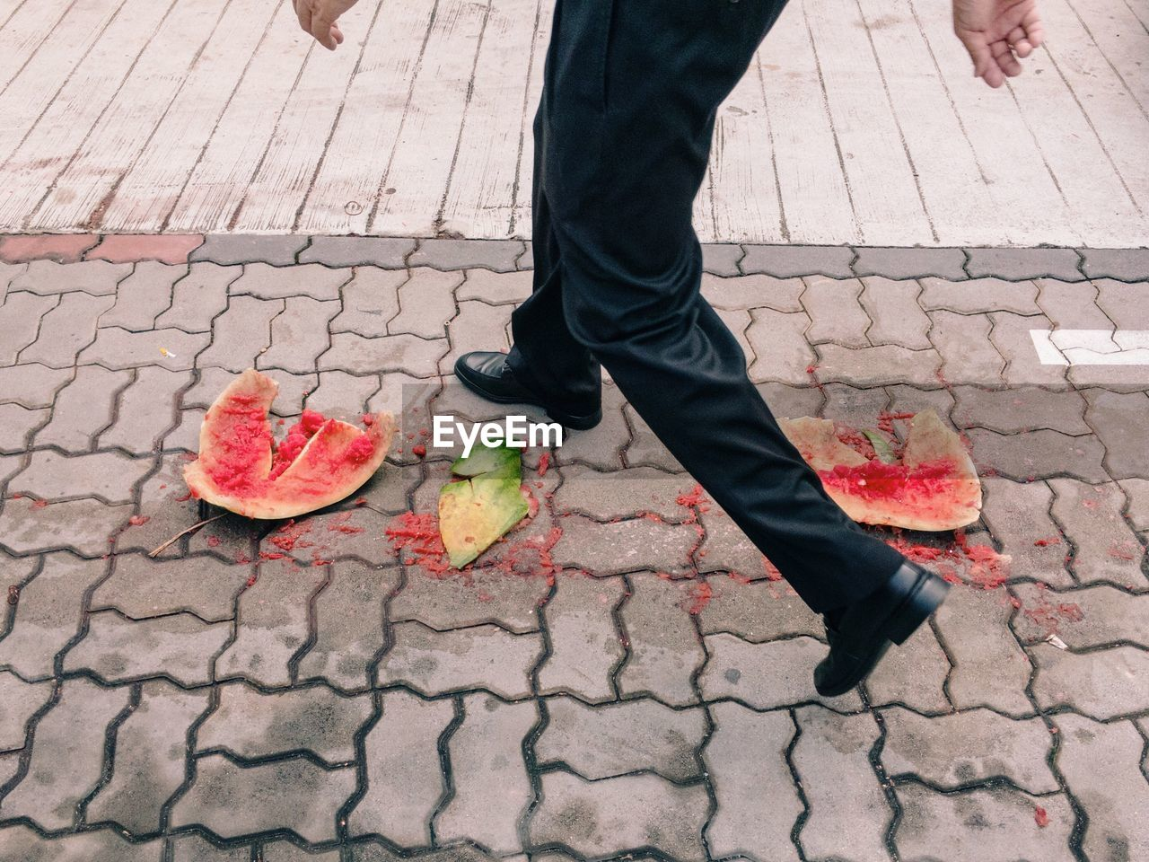 Low Section Of Man Walking Over Crushed Watermelon