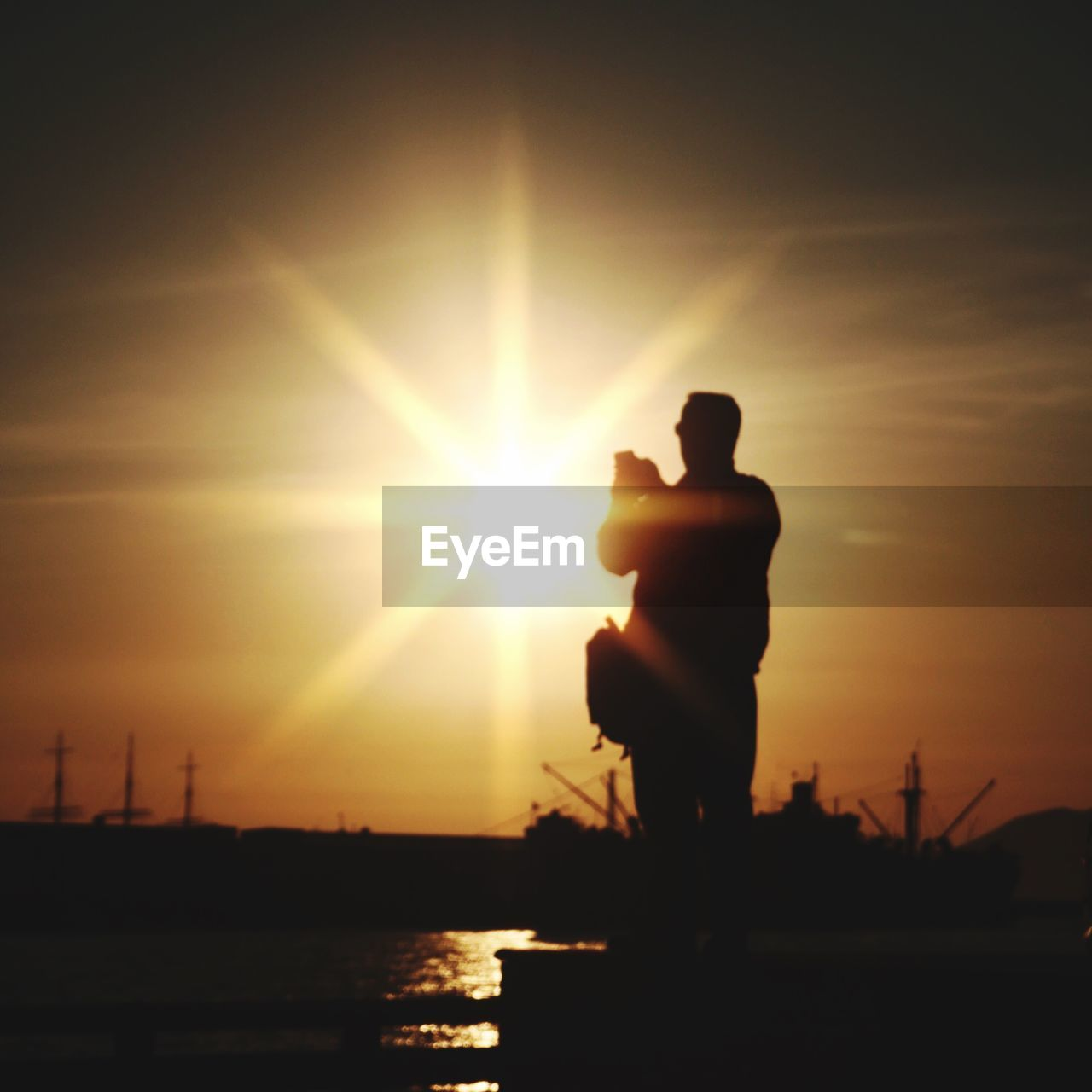Silhouette Of Man Taking Pictures Of Sunset Over Sea