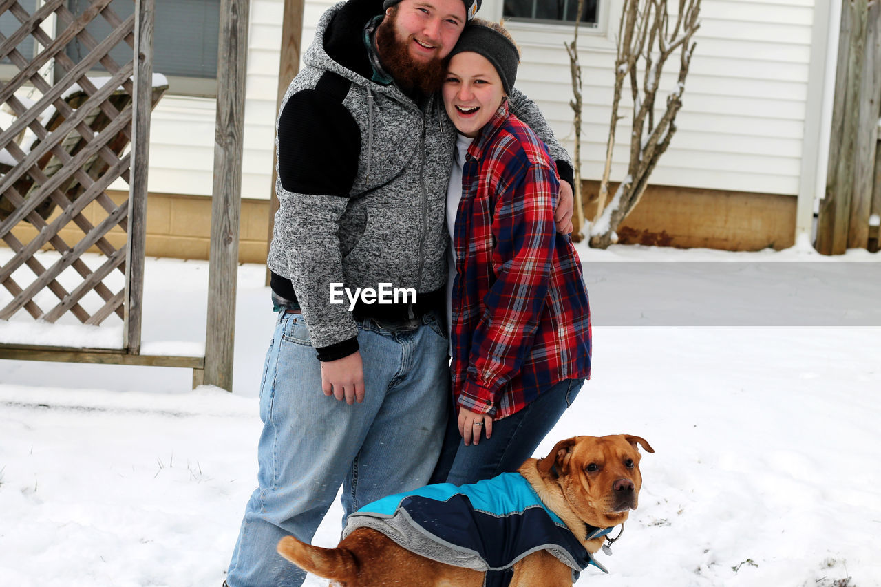togetherness, dog, two people, real people, pets, love, winter, day, cold temperature, bonding, animal themes, smiling, happiness, mammal, standing, young women, built structure, domestic animals, full length, building exterior, outdoors, snow, architecture, friendship, young adult, warm clothing
