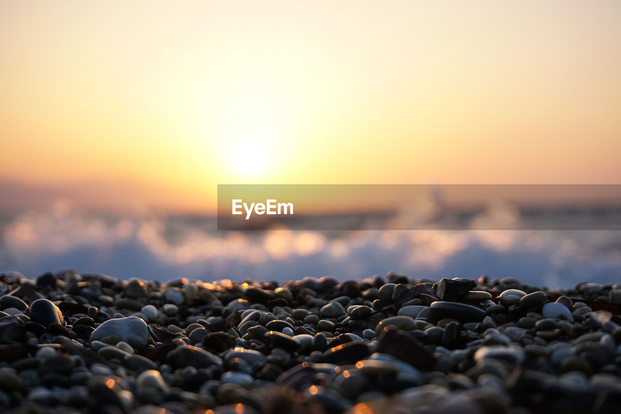 Close-Up Of Pebbles On Beach Against Sky During Sunset