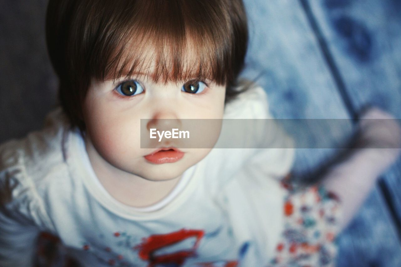 High Angle Portrait Of Cute Baby Girl At Home