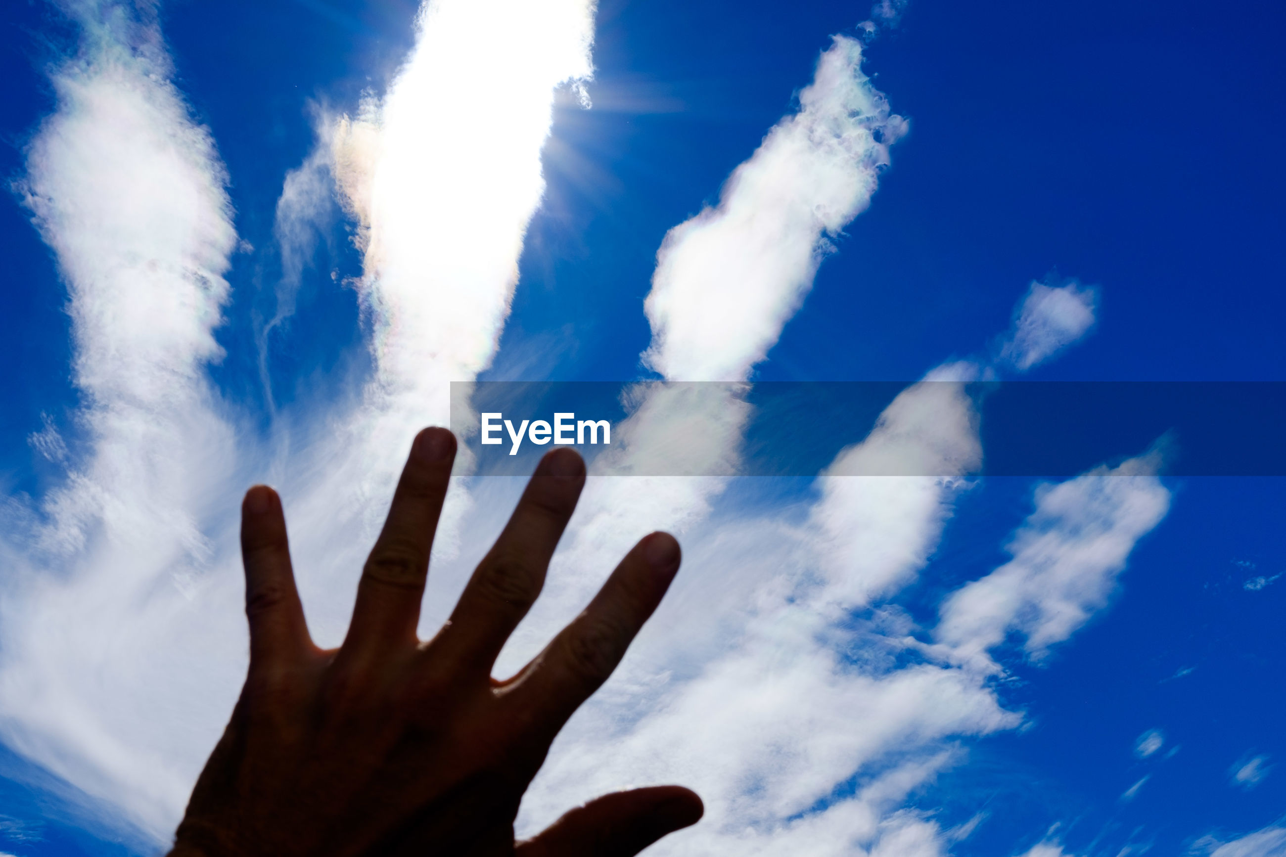 sky, human hand, cloud - sky, human finger, low angle view, human body part, reaching, day, outdoors, blue, nature, real people, one person, beauty in nature, palm, people