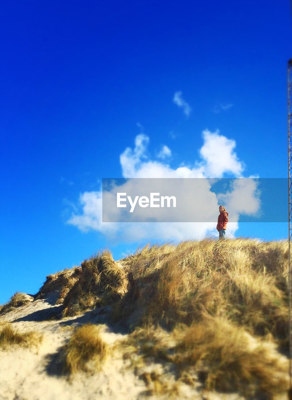 sky, one person, low angle view, real people, nature, blue, day, outdoors, cloud - sky, adventure, men, full length, beauty in nature, leisure activity, lifestyles, scenics, mountain, landscape, one man only, people