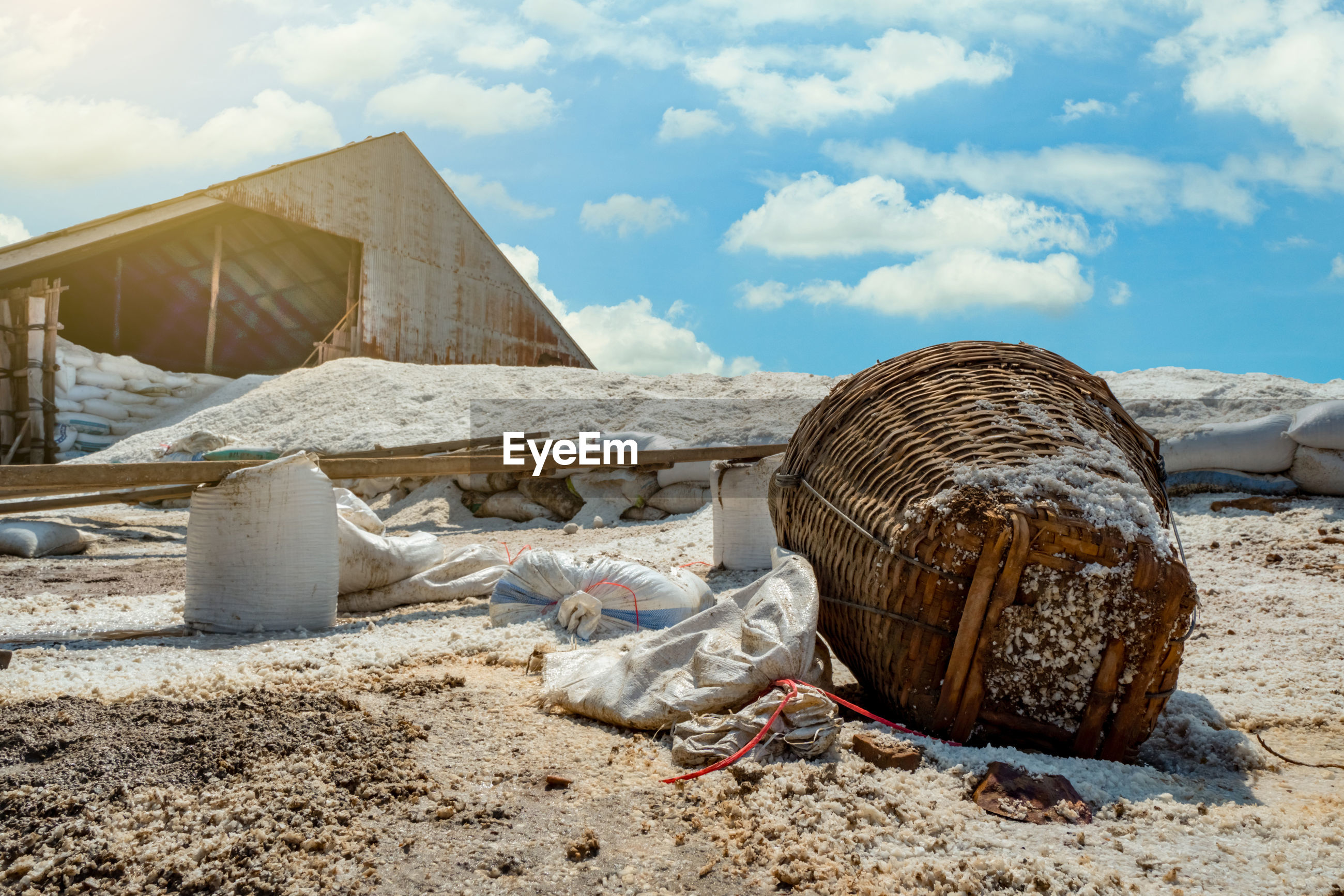 Barn with brine salt in sack. pile of organic sea salt and bamboo basket in front of barn with blue