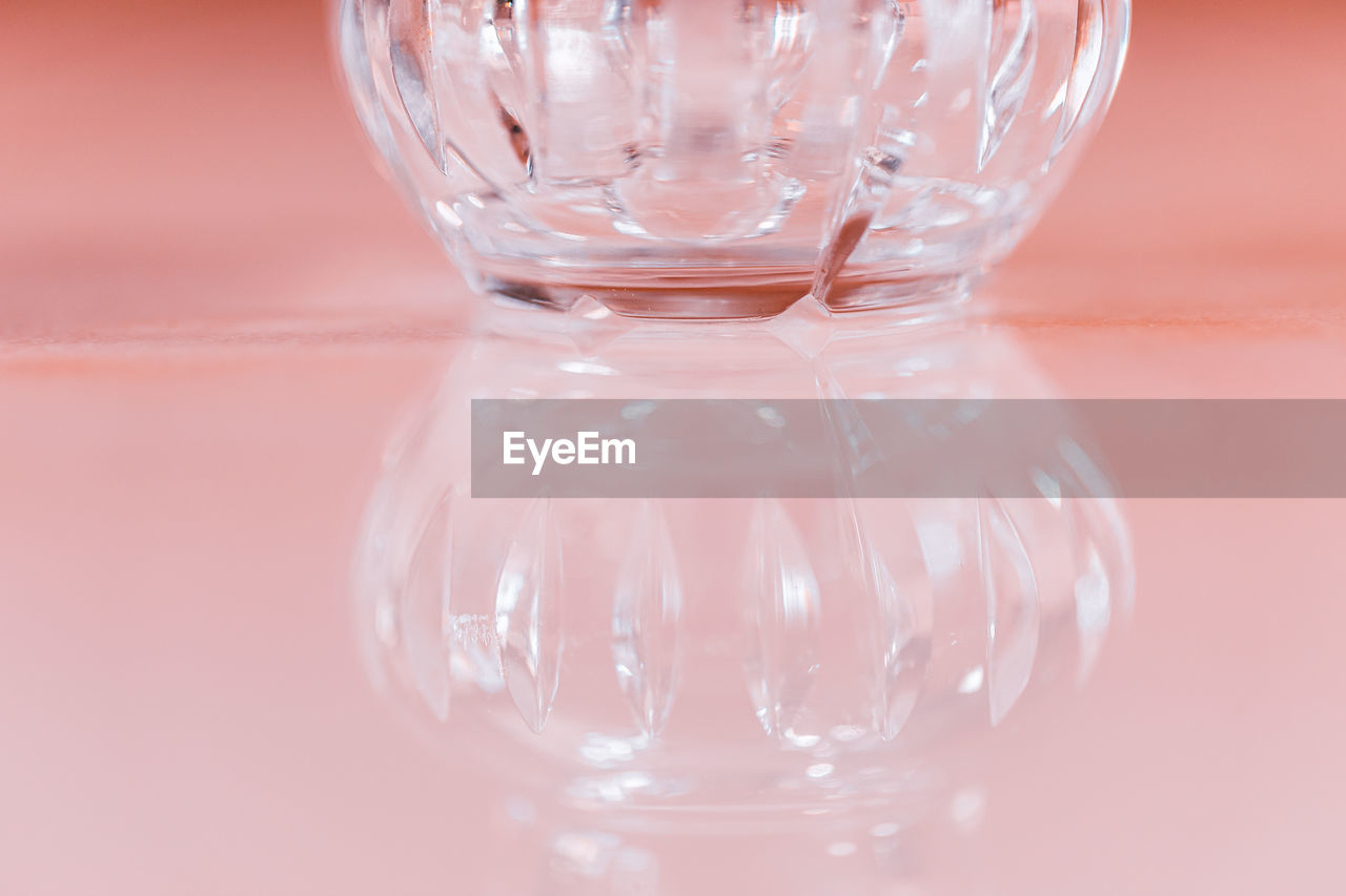 close-up, glass - material, indoors, transparent, still life, no people, studio shot, empty, glass, table, reflection, water, drinking glass, focus on foreground, container, single object, refreshment, pink color, colored background, crockery