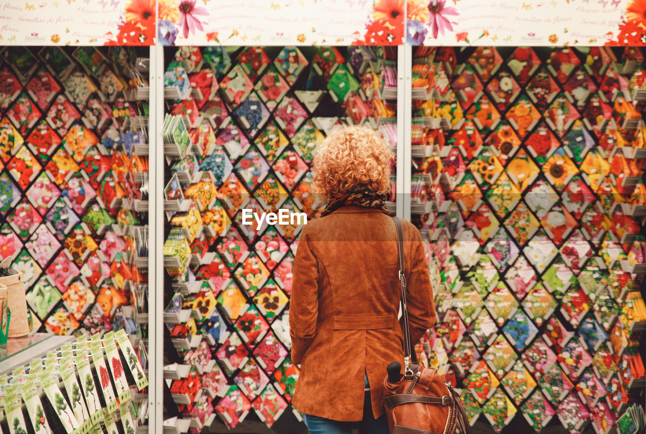 Rear View Of Woman Looking At Flower Seed Packets At Market