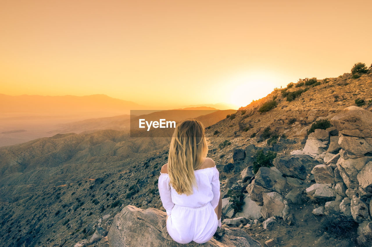 Rear view of woman sitting on rock against sky during sunset