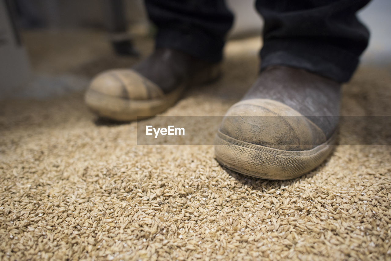 LOW SECTION OF MAN WITH BALL ON FLOOR