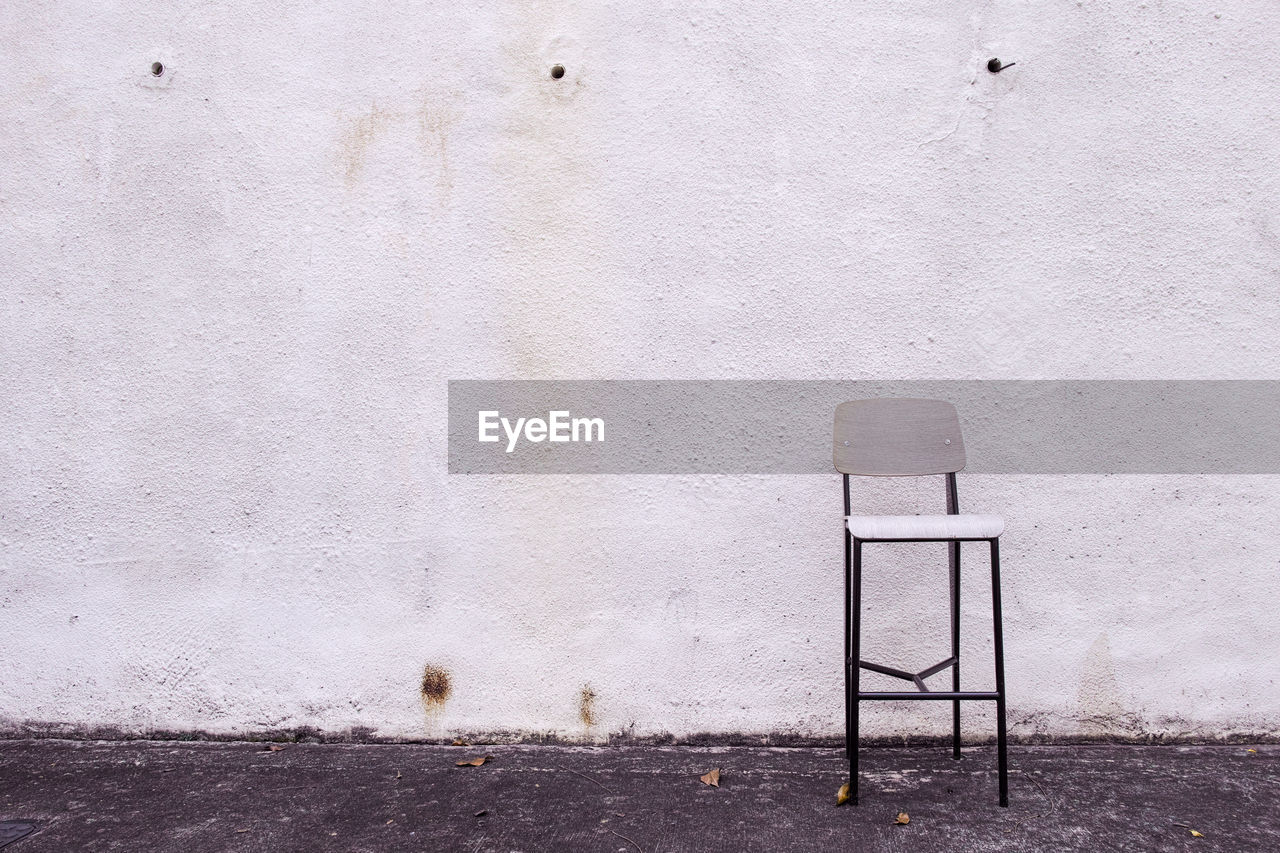 Empty Chair Against White Wall