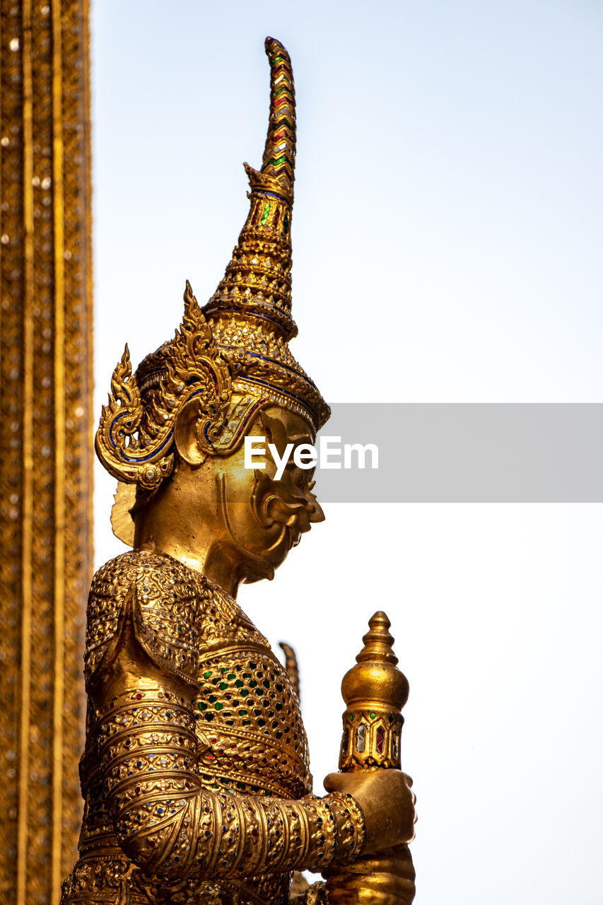 sculpture, statue, architecture, religion, art and craft, spirituality, belief, built structure, human representation, representation, building, place of worship, creativity, sky, no people, gold colored, male likeness, low angle view, outdoors, ornate, spire