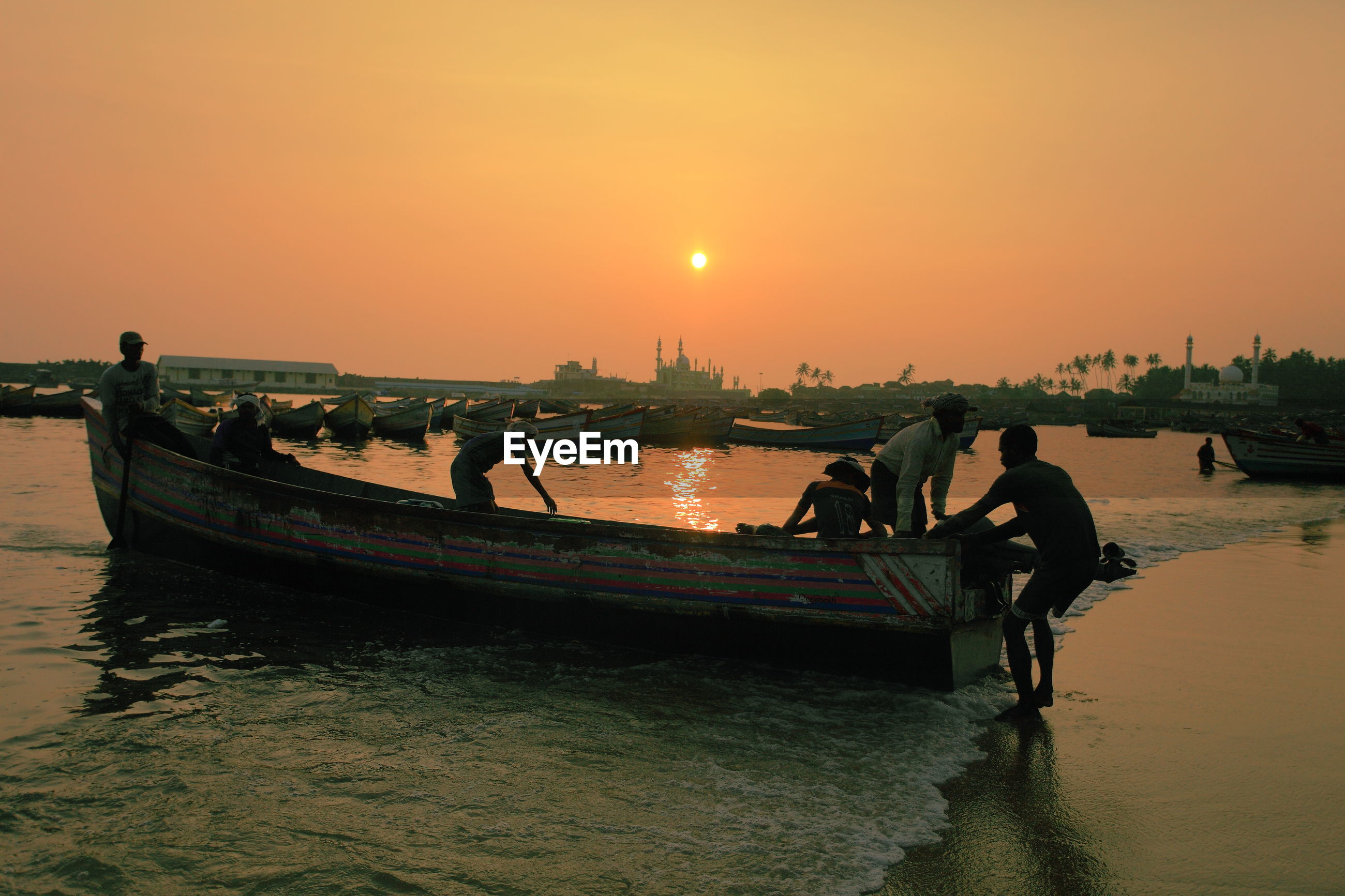 Men pulling out fishing boat in sea at sunset