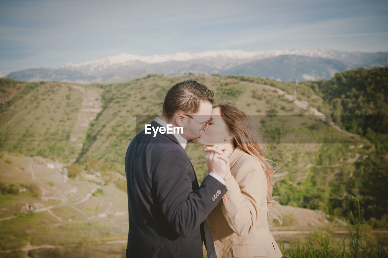 Couple Kissing With Mountains In Background