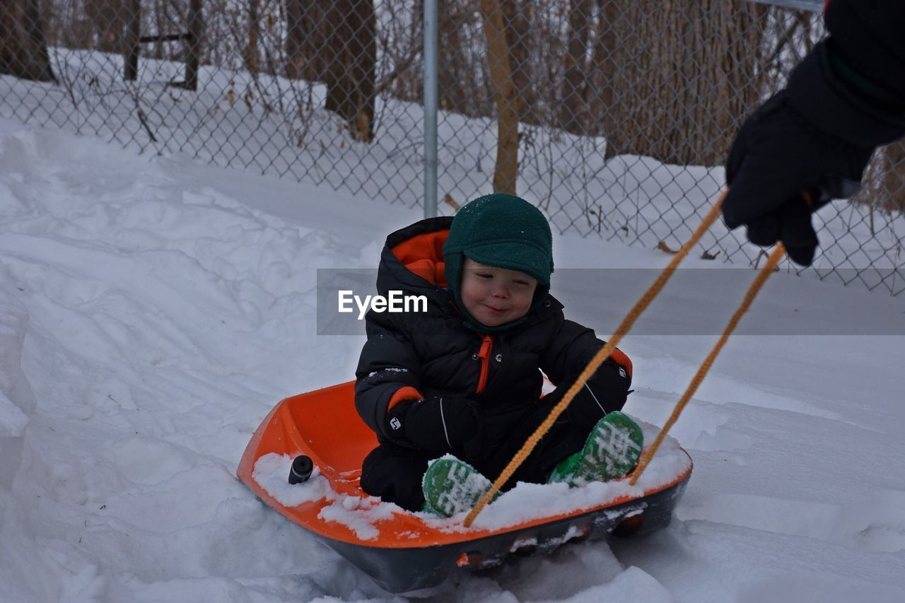 Boy sitting on toboggan pulled by his father