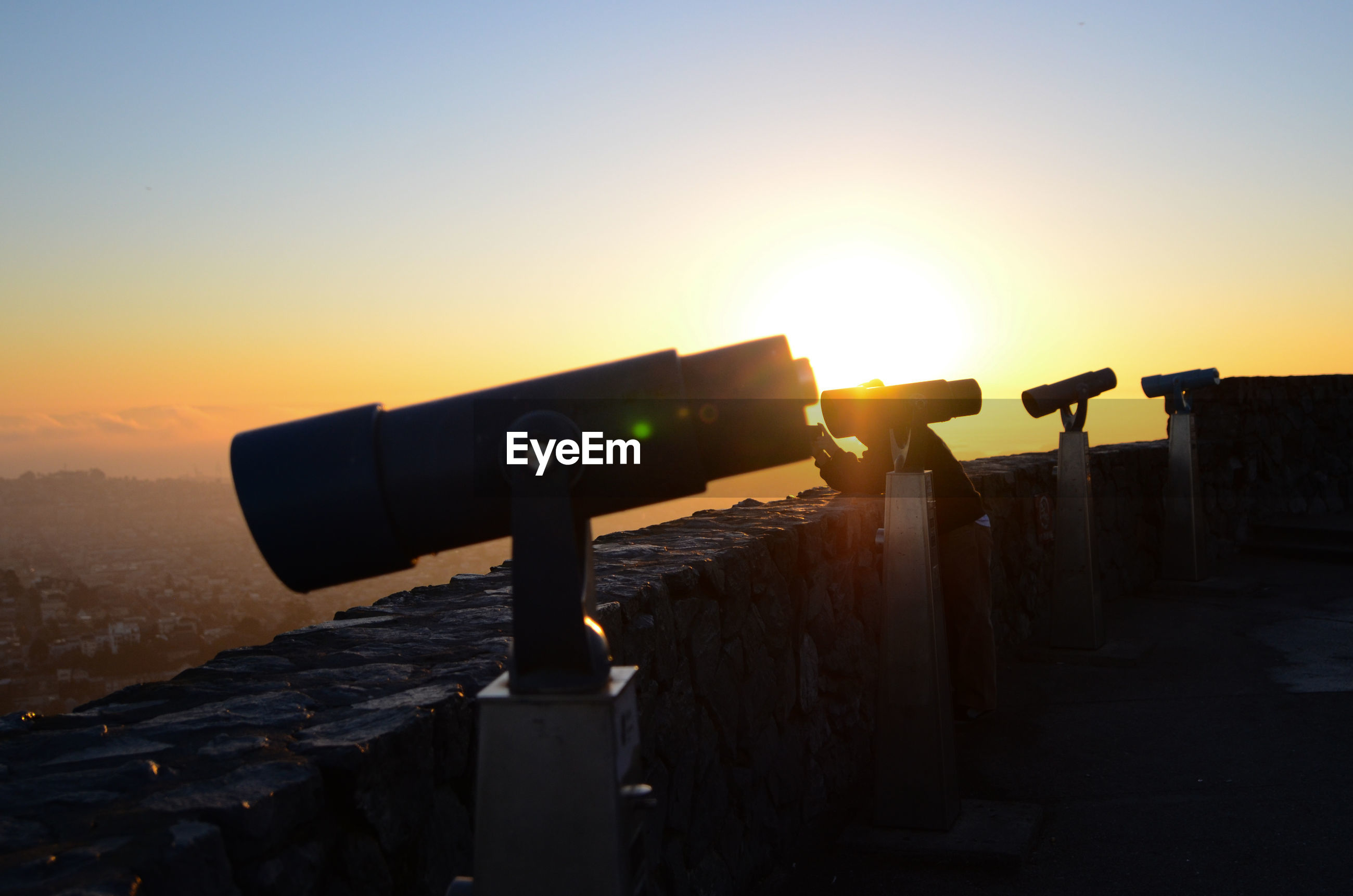 Silhouette of coin operated binoculars at sunrise