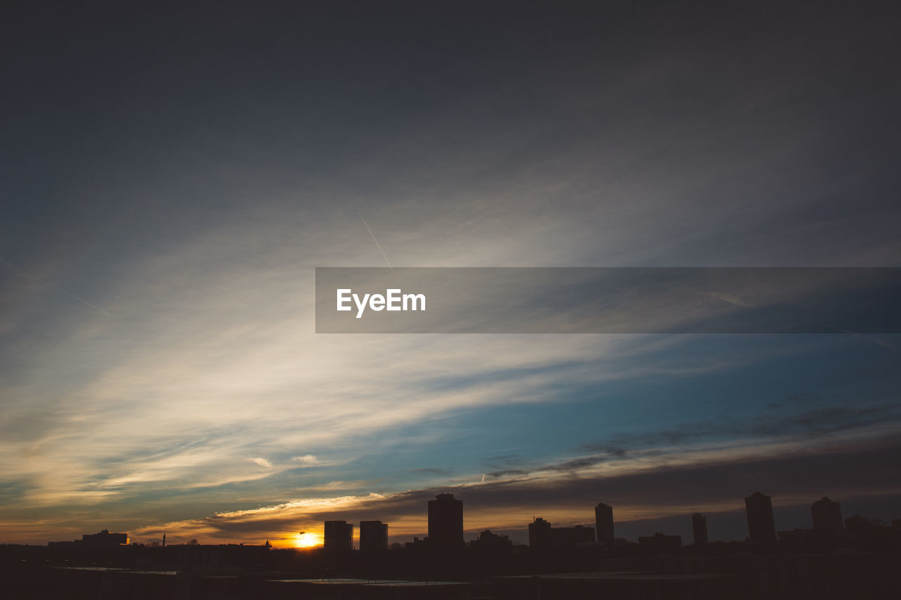 Idyllic view of silhouette city during against cloudy sky sunset