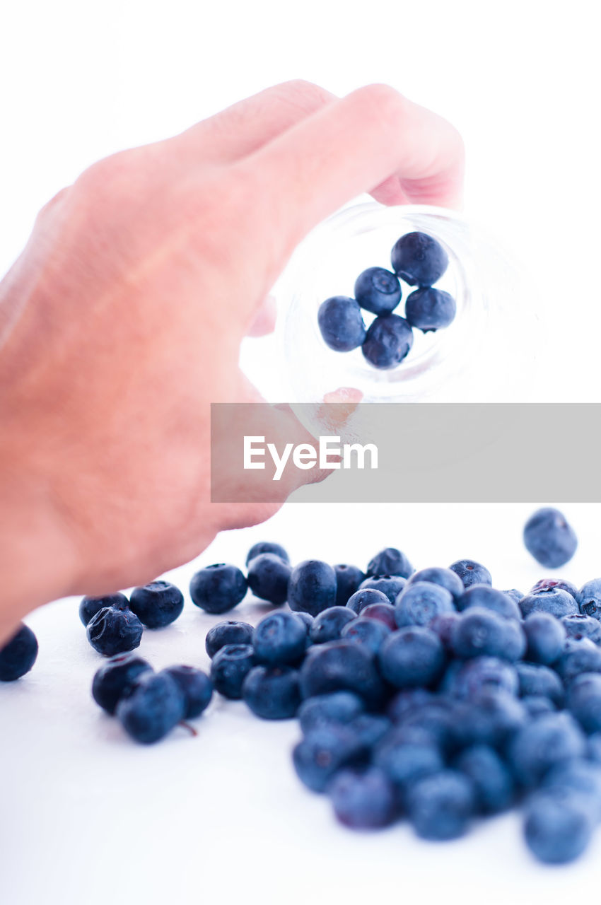 Close-up of human hand holding blueberries in glass against white background