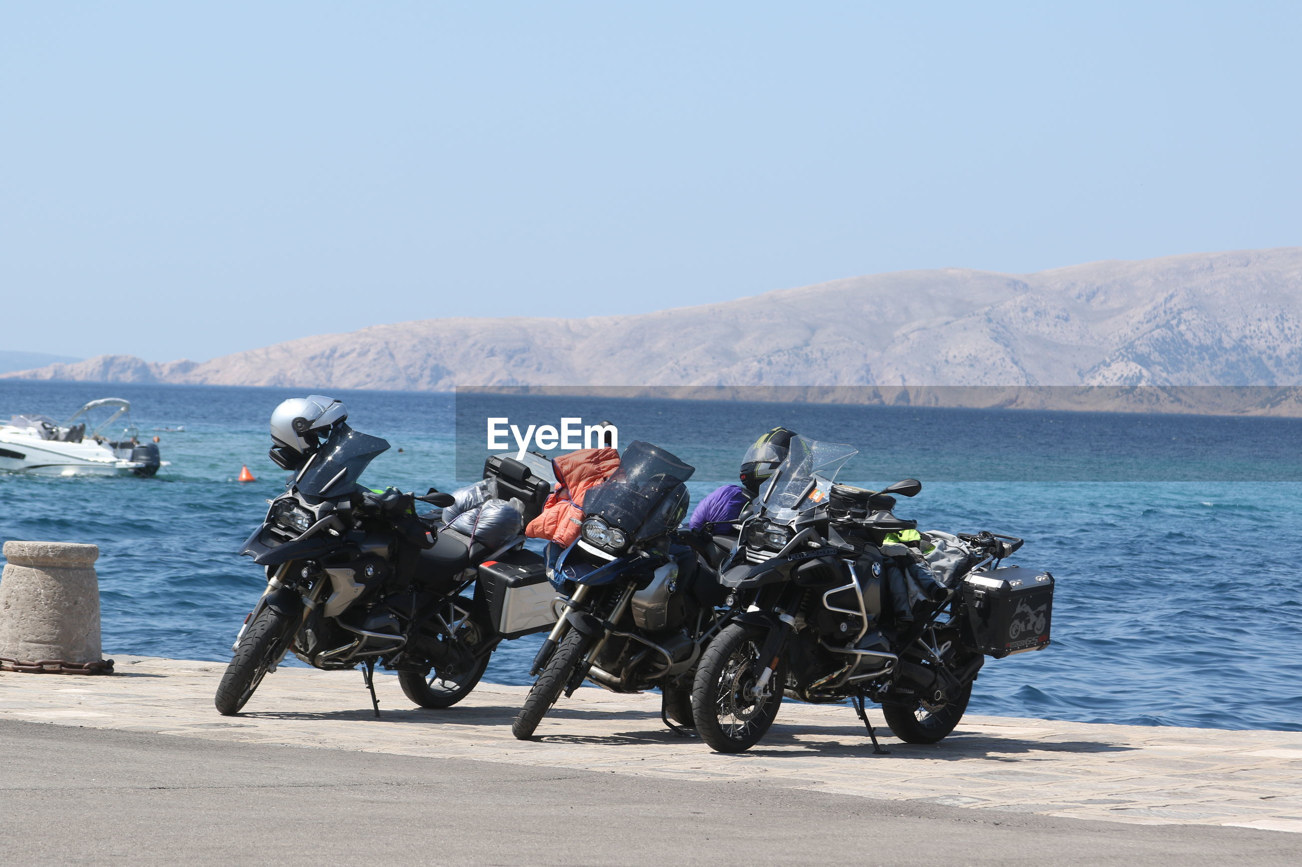 Motorcycles by sea against clear sky