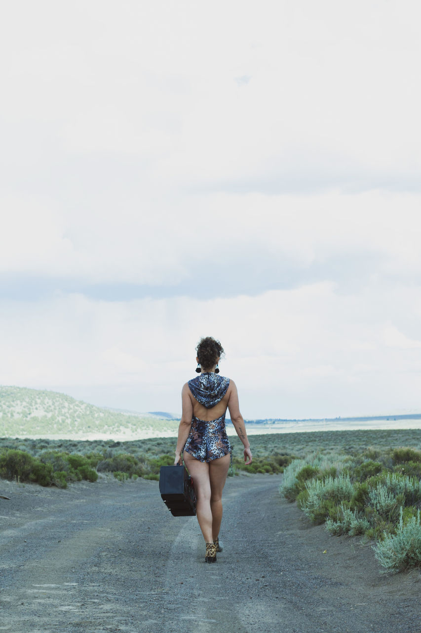 Rear View Of Woman With Suitcase Walking On Road Against Sky