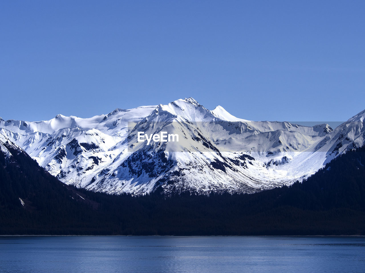 Idyllic shot of snowcapped mountain by river against clear blue sky