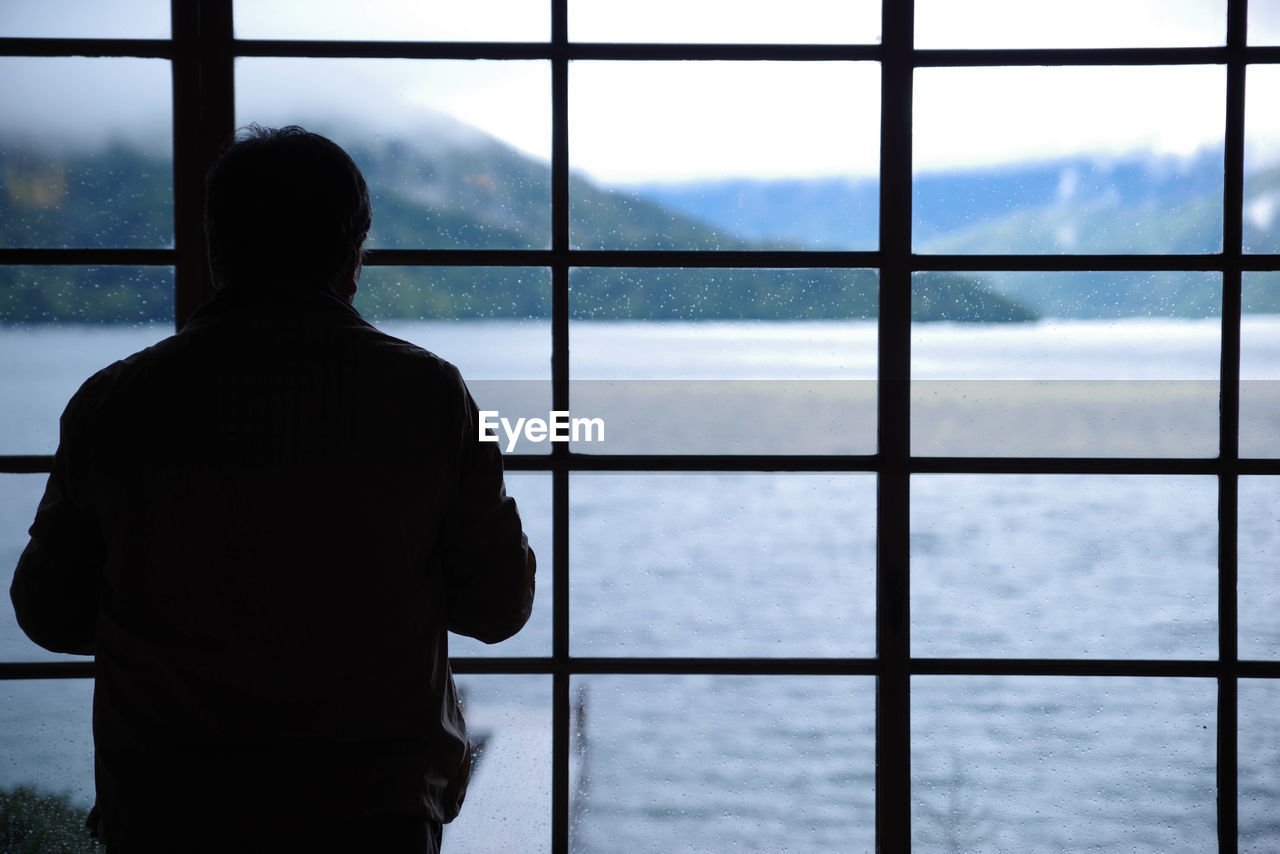 Rear View Of Silhouette Man Looking At Window