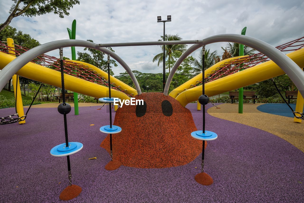 playground, yellow, park, park - man made space, childhood, day, outdoor play equipment, metal, nature, multi colored, outdoors, circle, shape, cloud - sky, sky, close-up, geometric shape, built structure, fun, merry-go-round