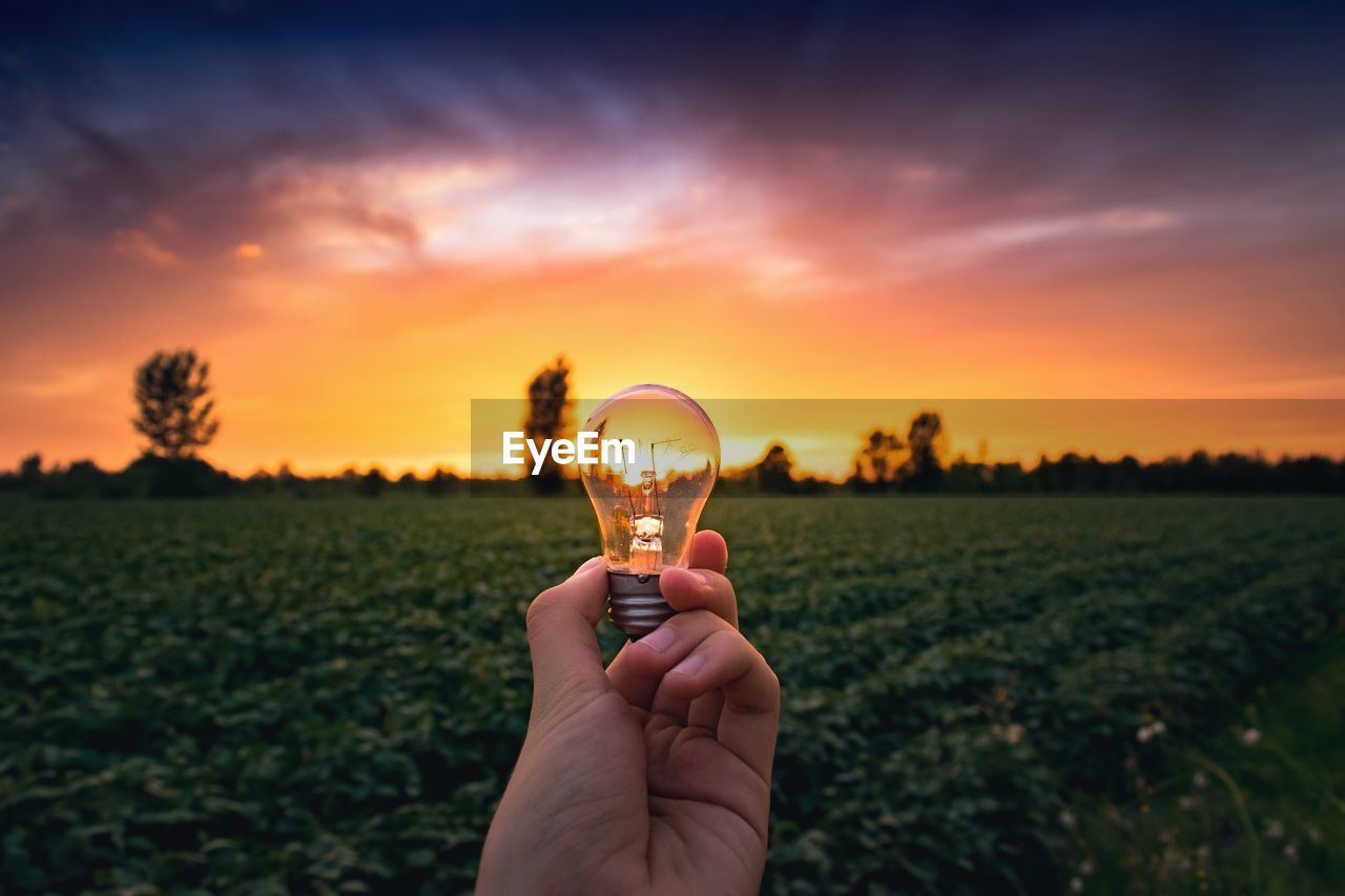 Cropped Hand Of Woman Holding Illuminated Light Bulb Against Field During Sunset