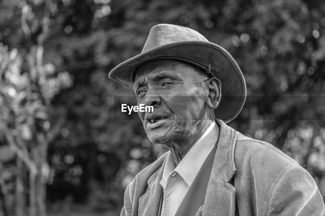 A headshot of an elderly man addressing people