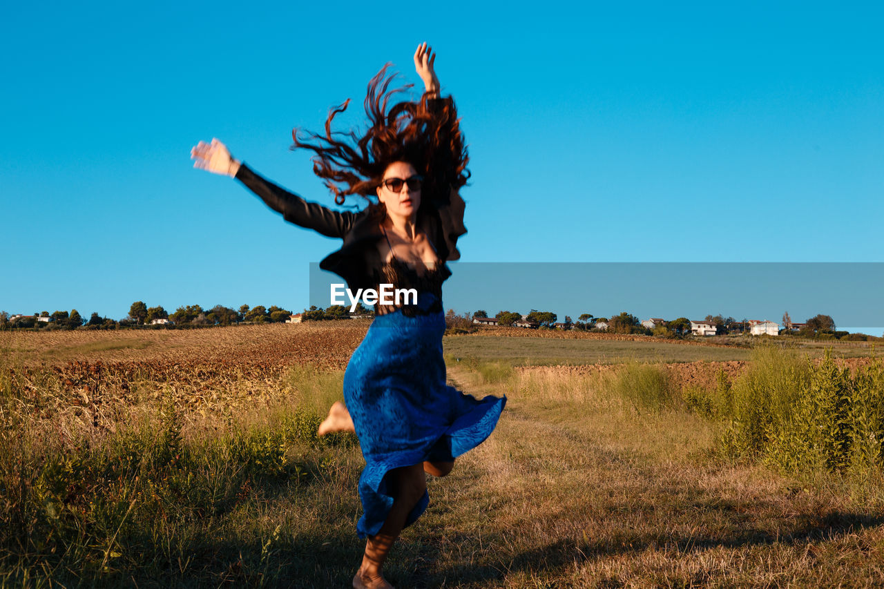 Full length of woman jumping on land against blue sky
