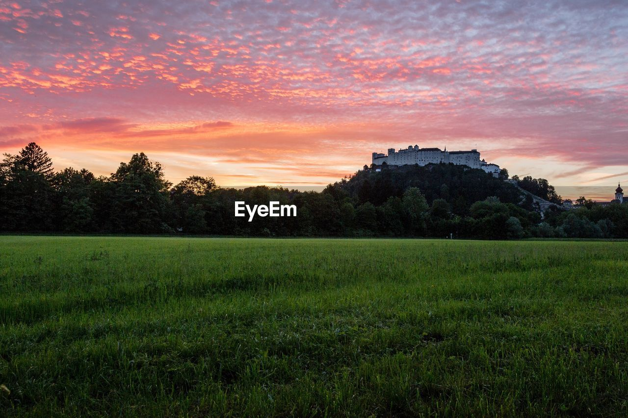 Scenic view of palace against dramatic sky during sunset