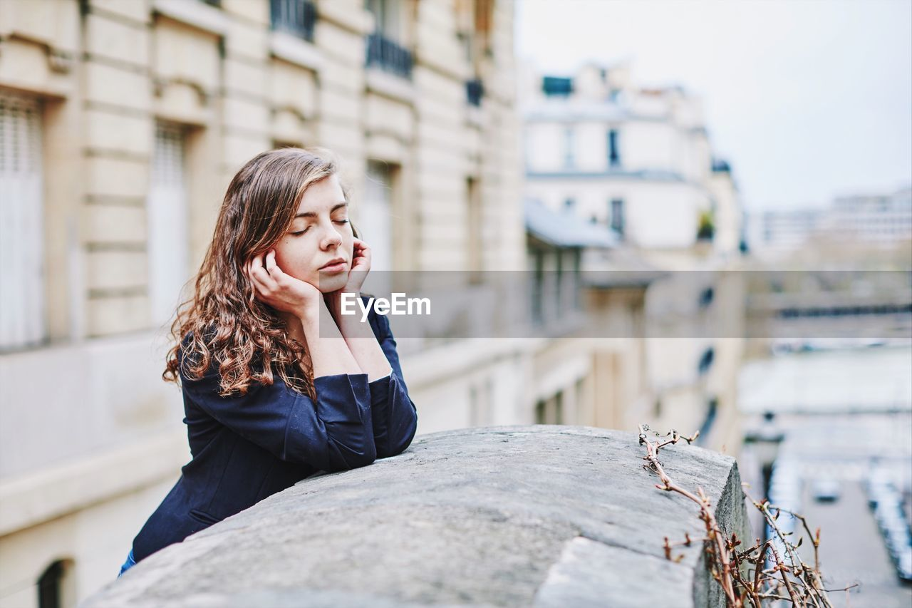 Young Woman With Eyes Closed Leaning On Concrete Wall