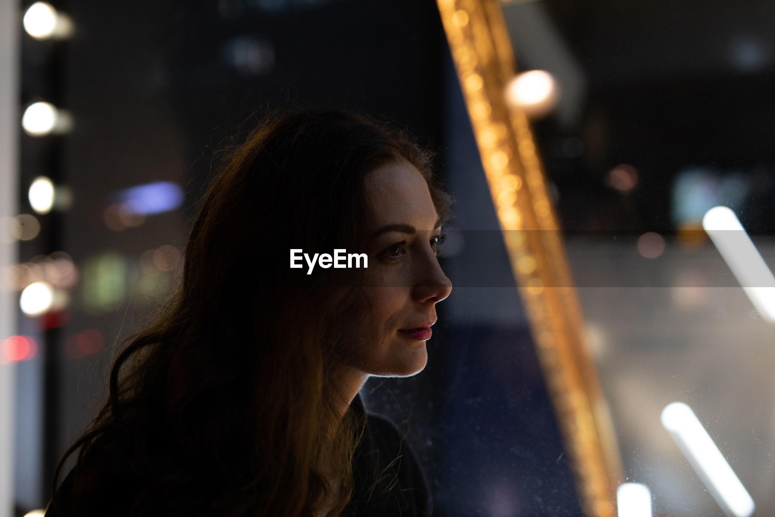 Woman looking away at night