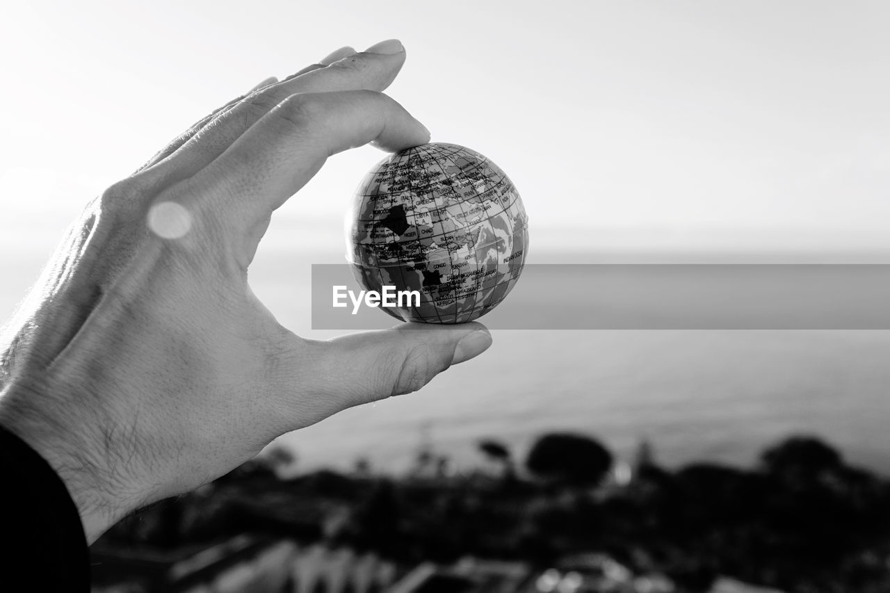 Close-up of hand holding globe against sky