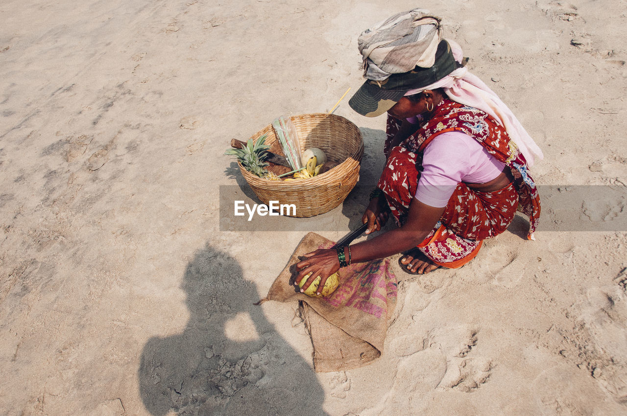 HIGH ANGLE VIEW OF WOMAN WORKING WITH BASKET