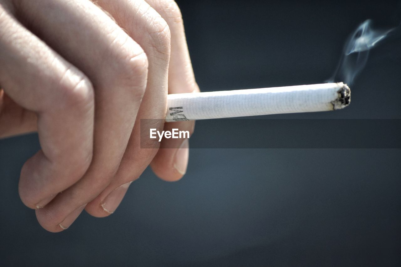 smoking issues, bad habit, cigarette, addiction, human body part, human hand, smoking - activity, risk, social issues, close-up, one person, lifestyles, real people, indoors, day, people