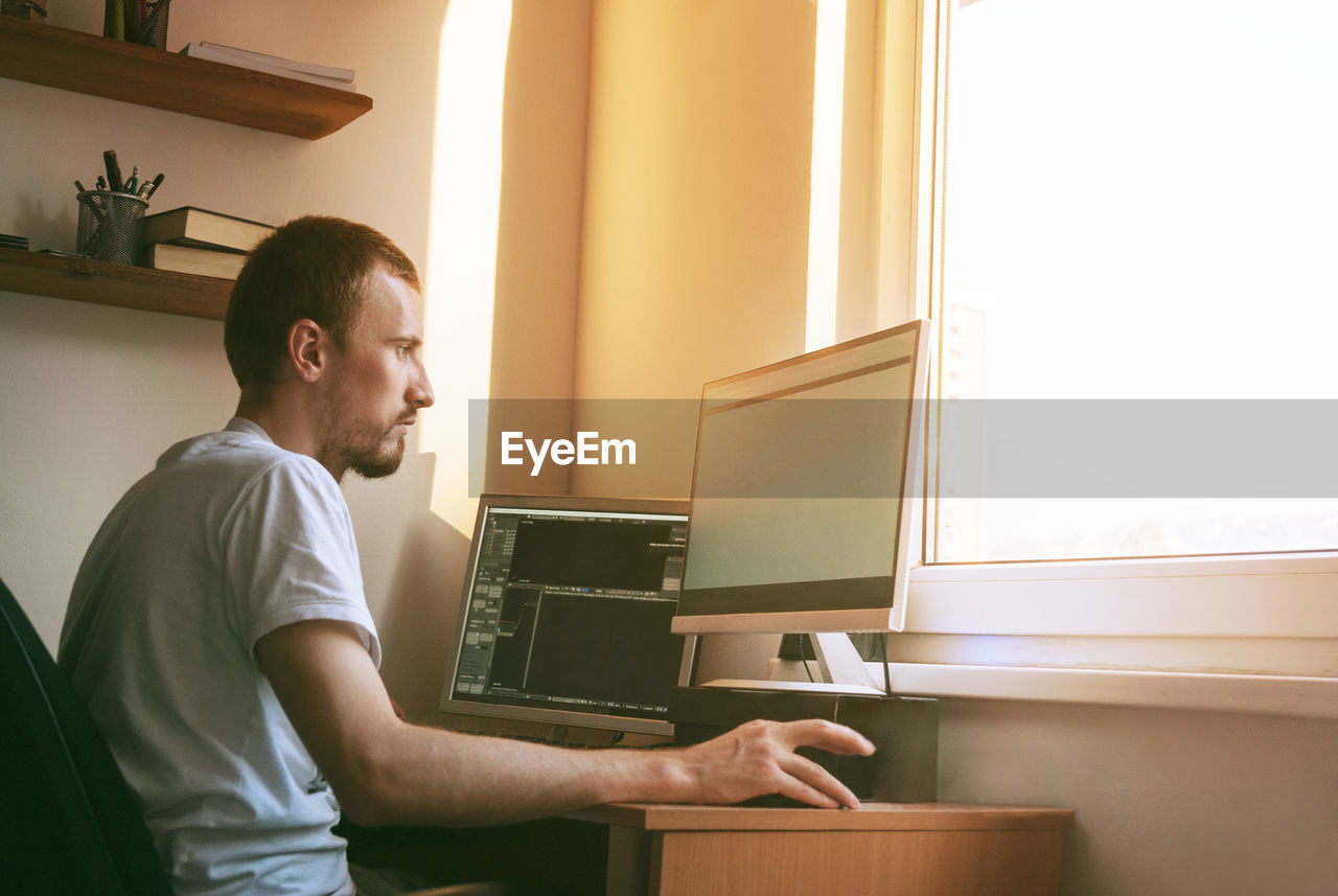 Side view of man working on laptop at home