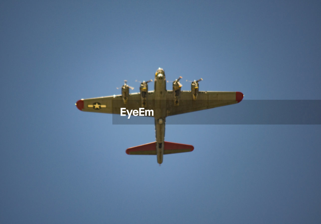 clear sky, copy space, low angle view, airplane, flying, transportation, blue, air vehicle, outdoors, day, no people, sky