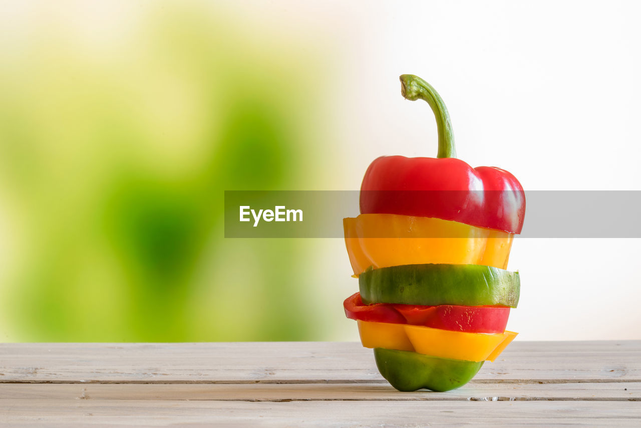 food and drink, food, vegetable, wood - material, freshness, table, healthy eating, red, pepper, still life, focus on foreground, bell pepper, green color, wellbeing, close-up, no people, fruit, yellow, tomato, orange color