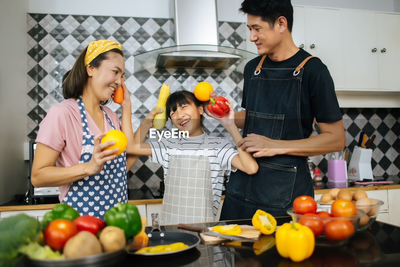 Family holding food in kitchen at home