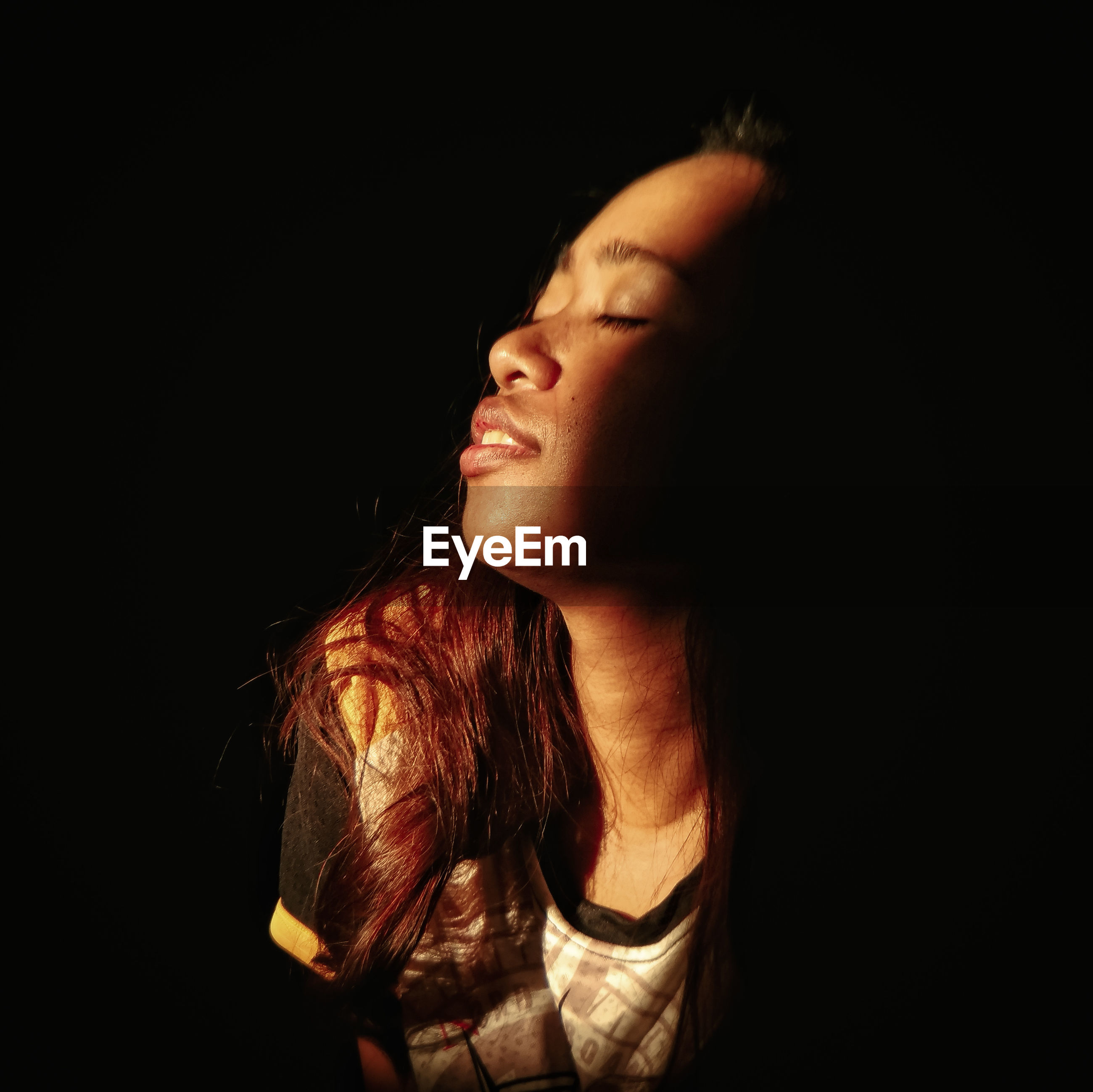 Young woman with eyes closed against black background